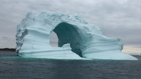 disko : Iceberg arch like Darwin arch in Galapagos Islands. Fantastic wonderful amazing video grenland nature iceland. Lovely shooting the life of nature, seaside and mountains. Global warming.