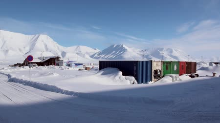 takımadalar : LONGYEARBYEN, SVALBARD - 23 APRIL, 2015: Landscape and buildings, roads in Small town Longyear among snow capped mountains of Norwegian archipelago of Svalbard in early spring in Norway.