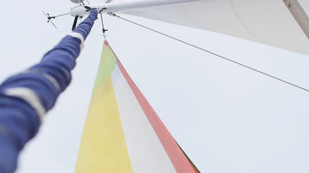 lanoví : Multicolored Sailing in the wind through the waves. Full sails, very strong wind. Ocean race, real adventure. Real spray. Sun sails, and adventure. Sail blows in the wind on a boat. Slow motion shot.