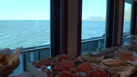 cancellation : Bread, watermelon, lettuce, sauce and other food on the ship with a view of the ocean. Table setting. Panorama. Cruise Iceland.