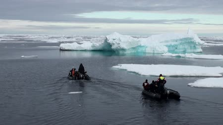 underwater landscape : Iceland- 8 September 2016: TTwo rubber boats with divers floating near icebergs, ice in Arctic Ocean. Extreme tourism and travel in cold polar north. Scenic blue water.