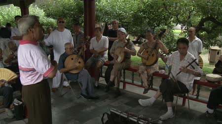 elnök : Beijing, China - 12 August 2015: Musicians on streets of city in park. National traditions of modern family on background of public traffic of crowd in Asia.