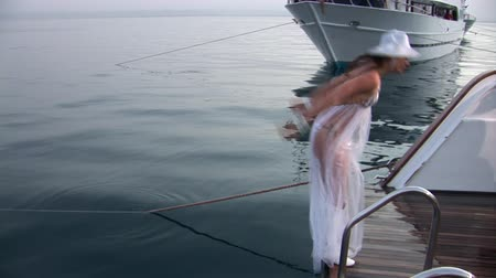 looking towards : Free diver model on ship near water in Red Sea. Filming a movie. Young girl smiling at camera.