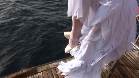 looking towards : Model in costume of angel clothes pointe shoes on ship near water in Red Sea. Filming a movie. Young girl smiling at camera.