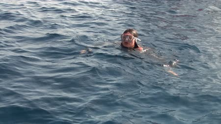 looking towards : Woman diver dives into flippers underwater in Red Sea. Filming a movie. Young girl smiling at camera.