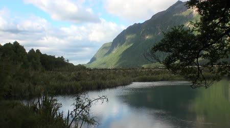 Új zéland : Unique lake in green mountains calm water of New Zealand. Beautiful background of amazing nature. Travel and tourism in the world of wildlife. Stock mozgókép