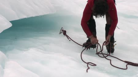 alpinista : New Zealand, 12 October 2013: Male climber fixing the mount on glacier in snowy cold mountains. Ideal place for extreme mountaineering. Beautiful landscape nature. Travel and tourism in wildlife. Stock Footage