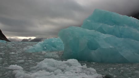 takımadalar : Iceberg in the water of Arctic Ocean on background of mountain in Svalbard. Wildlife in Nordic badlands. Unique footage on background natural landscape and snow of Spitsbergen.