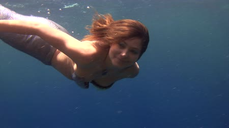 sualtı : Underwater model free diver swims in clean transparent blue water in Red Sea. Young girl smiling at camera. Filming a movie in marine landscape, coral reefs, ocean inhabitants. Stok Video