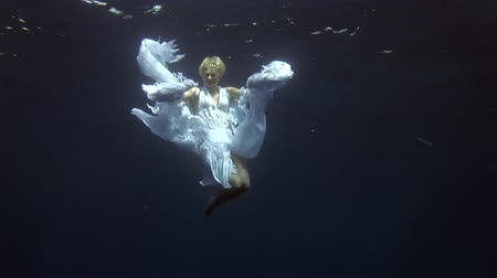 looking towards : Underwater model free diver in costume angel swims in clean water in Red Sea. Filming a movie. Young girl smiling at camera. Extreme sport in marine landscape, coral reefs, ocean inhabitants. Stock Footage
