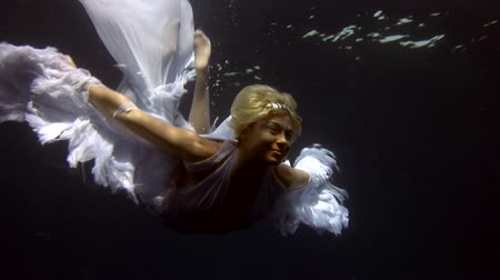 sereia : Underwater model free diver in costume angel swims in clean water in Red Sea. Filming a movie. Young girl smiling at camera. Extreme sport in marine landscape, coral reefs, ocean inhabitants. Stock Footage