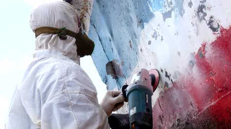 rasp : Working people tear off paint on metal in repairs process at shipyard. Workers in overalls reconstruct at ship repair yard outdoors in port.