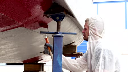 lower part : Worker paints metal of lower part of ship red color at shipyard in port. Repair and reconstruction of sea vessel. Outdoor work. Technology of manual painting boats. Industry of water transport.