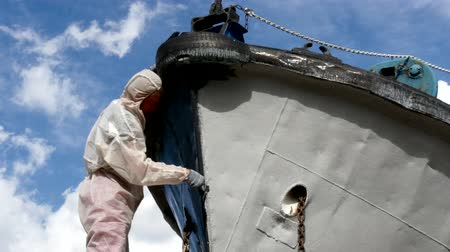 pervane : Worker paints with brush metal front of ship at shipyard in port of Moscow. Process of repair of sea vessel. Outdoor work. Technology of manual painting boats. Industry of water transport.