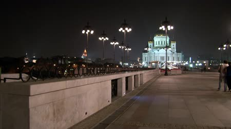 saviour : Moscow, Russia - 16 August 2010: People walk along Patriarchal bridge to Cathedral of Christ Savior at night. Architecture and glowing golden domes of orthodox temple. Bright streets and city lights.