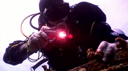 abyss : Red Sea, Egypt - 21 June 2015: Scuba divers swimming explore shipwreck Salem Express deep underwater. Secret of sunken ship which crashed on coral reef. Historical place of tragedy.