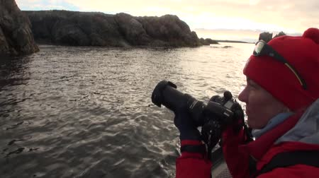 takes : Spitsbergen, Norway - 14 August 2016: Tourist takes pictures photographs in boat sail cost of Arctic Ocean Svalbard. Wildlife in Nordic badlands.