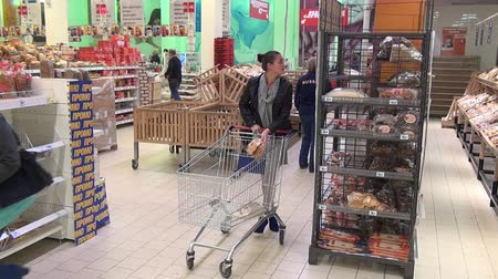baharatlı alman sosisi : Moscow, Russia - 20 May 2016: Woman buys bread in the supermarket baking department. People buy foodstuffs. Retail Food Industry. Stok Video