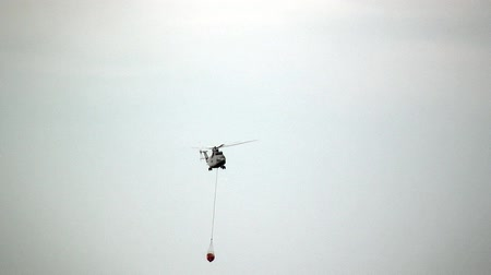 водослива : Alabino, Russia - August 22, 2017: Cargo fire helicopter with suspended spillway ladle is flying from reservoir. Special equipment with water on gray sky background. Forum Army 2017. Стоковые видеозаписи