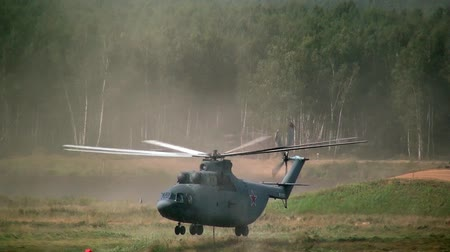 suspensão : Alabino, Russia - August 22, 2017: Military helicopter lands on a clearing near forest. Special equipment on Forum Army 2017.