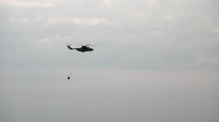 водослива : Alabino, Russia - August 22, 2017: Cargo fire helicopter with suspended spillway ladle takes water from reservoir. Special equipment on Forum Army 2017.