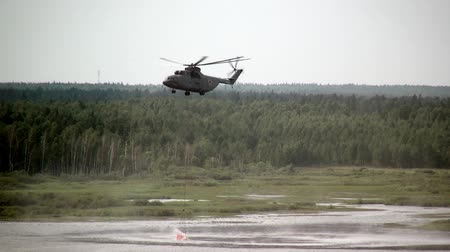 водослива : Alabino, Russia - August 22, 2017: Cargo fire helicopter with suspended spillway ladle takes water from reservoir. Special equipment with water on gray sky background. Forum Army 2017.