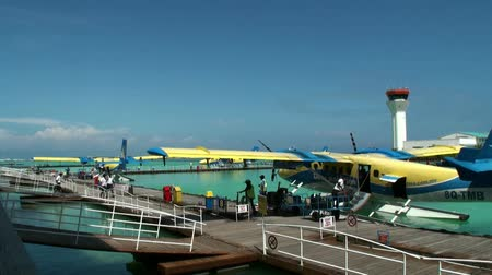 hydroplane : Maldives, Indian Ocean - 12 September 2017: Yellow-blue hydroplane is near pier on background water surface in ocean. Water and air transport for tourists.