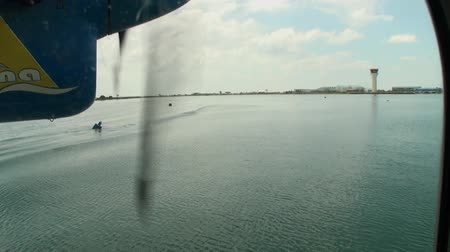 hydroplane : Maldives, Indian Ocean - 12 September 2017: Screw of the yellow-blue plane spins on the background of the ocean. Water and air transport for tourists.