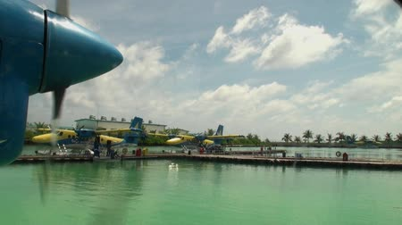 hydroplane : Maldives, Indian Ocean - 12 September 2017: Screw of the yellow-blue plane spins on background of pier. Water and air transport for tourists.