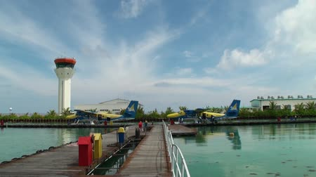 hydroplane : Maldives, Indian Ocean - 12 September 2017: Yellow-blue hydroplane stands near pier in ocean. Water and air transport for tourists. Stock Footage