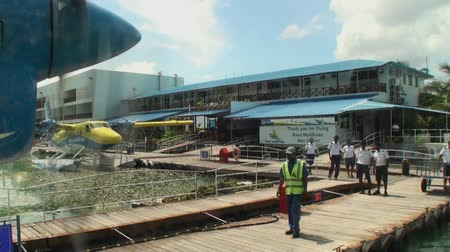 silêncio : Maldives, Indian Ocean - 12 September 2017: Screw of the yellow-blue plane spins on background of pier. Water and air transport for tourists.
