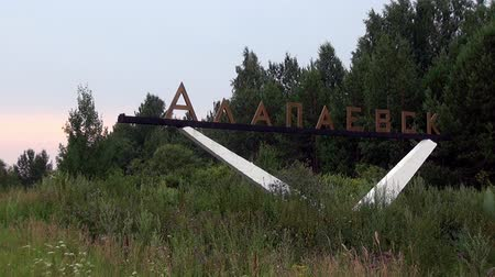 metallurgical : Alapaevsk, Russia - 17 July 2012: Stela at the entrance to city. Large monumental design with designation of citys name and symbols in form of coat of arms and logoin. Made of concrete and metal.