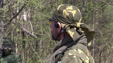 komutan : Moscow, Russia - May 09, 2013: Commander of the gaming team in military uniform gives an installation on game. Airsoft men in summer outfit are in the forest near the ruins.