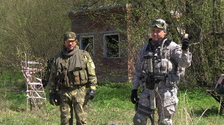командир : Moscow, Russia - May 09, 2013: Commander of the gaming team in military uniform gives an installation on game. Airsoft men in summer outfit are in the forest near the ruins.