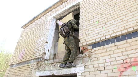 hiding : Moscow, Russia - May 09, 2013: Airsoft men in military uniform with a weapon climbs up the ruined house. Sports team game using a copy of a firearm. Stock Footage