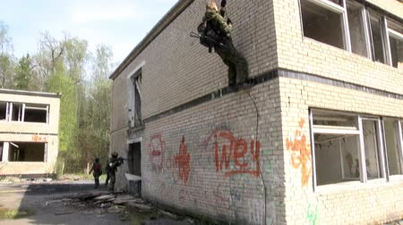 granada : Moscow, Russia - May 09, 2013: Airsoft men in military uniform with a weapon climbs up the ruined house. Sports team game using a copy of a firearm. Vídeos