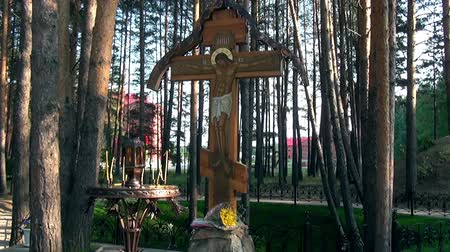 romanov : Alapaevsk, Russia - 17 July 2012: Candles near cross with crucifix in place of execution of Elizabeth Feodorovna. History of last days of life of relatives of Russian Emperor Nicholas II Romanov.