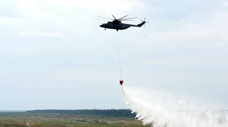 водослива : Alabino, Russia - August 22, 2017: Red hanging scoop from a fire helicopter dumps water on gray sky background. Special equipment with water for accidents and disasters. Forum Army 2017. Стоковые видеозаписи