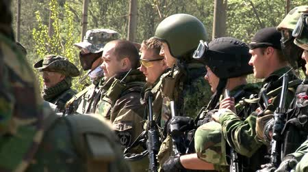hiding : Moscow, Russia - May 09, 2013: Airsoft team in military uniform with a weapon on background of forest. Sports game using a copy of a firearm.