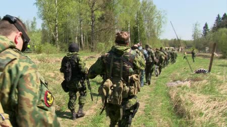 combate : Moscow, Russia - May 09, 2013: Players of airsoft in military uniform with weapon go to a position. Sports team game using a copy of a firearm.