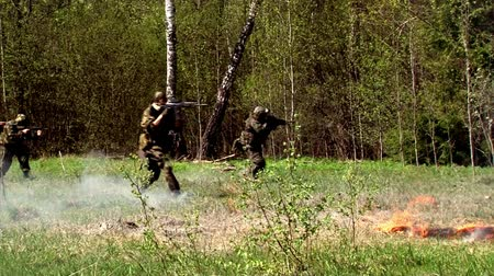 two forces : Moscow, Russia - May 09, 2013: Players of airsoft run through the woods Sports team game using a copy of a firearm. People in military uniforms with weapons at the exercises. Stock Footage