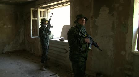bron : Moscow, Russia - May 09, 2013: Players of airsoft is in position in a destroyed house. Sports team game using a copy of a firearm. People in military uniforms with weapons at the exercises.