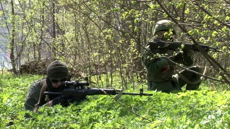 two forces : Moscow, Russia - May 09, 2013: Players of airsoft is in position in the forest. Sports team game using a copy of a firearm. People in military uniforms with weapons at the exercises. Stock Footage