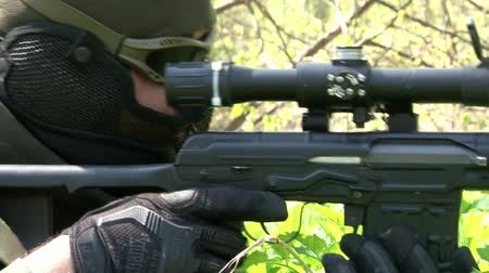 two forces : Moscow, Russia - May 09, 2013: Airsoft player is in position in the forest. Sports team game using a copy of a firearm. People in military uniforms with weapons at the exercises.