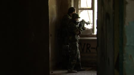 two forces : Moscow, Russia - May 09, 2013: Players of airsoft is in position in a destroyed house. Sports team game using a copy of a firearm. People in military uniforms with weapons at the exercises.