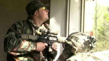 two forces : Moscow, Russia - May 09, 2013: Airsoft player is in position is in position in a destroyed house. Sports team game using a copy of a firearm. People in military uniforms with weapons at the exercises. Stock Footage