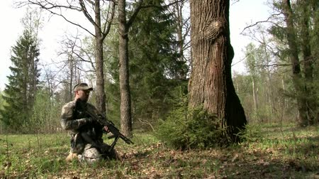 combate : Moscow, Russia - May 09, 2013: Players of airsoft is in position in the forest. Sports team game using a copy of a firearm. People in military uniforms with weapons at the exercises. Vídeos