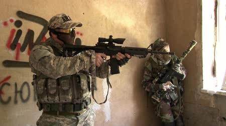 two forces : Moscow, Russia - May 09, 2013: Players of airsoft is in destroyed house. Sports team game using a copy of a firearm. People in military uniforms with weapons at the exercises.