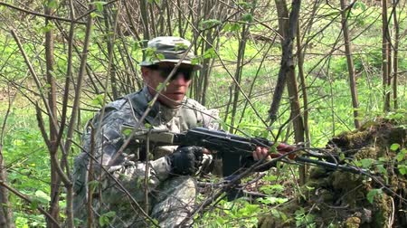 hiding : Moscow, Russia - May 09, 2013: Airsoft game in the forest. People in military uniforms with weapons at the exercises.