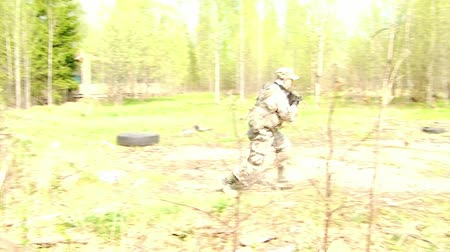 batalha : Moscow, Russia - May 09, 2013: Airsoft game on background of ruined building. People in military uniforms using a copy of a firearm.